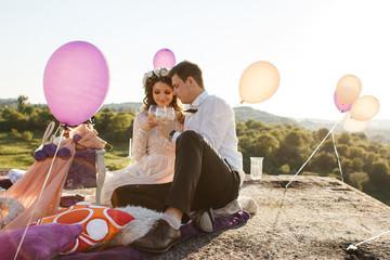 Smiling couple enjoys wine on the rood sitting among floating ba