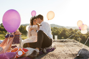 Happy newlyweds drink wine on the roof while colored balloons le