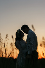 Silhouettes of stunning couple standing on the field in evening