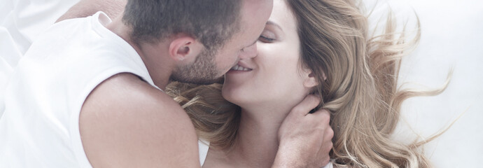 Love couple kissing in bed