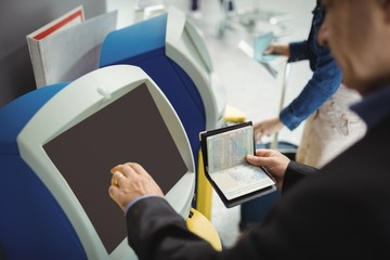 Businessman using self service check-in machine