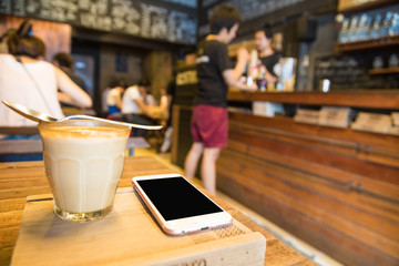Cup of lattecoffee on a wooden table with smartphone