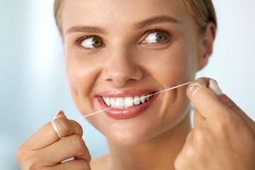 Dental Care. Woman With Beautiful Smile Using Floss For Teeth. High Resolution Image