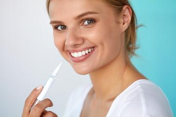 Teeth Whitening. Beautiful Woman Using Teeth Whitening Pen. High Resolution Image