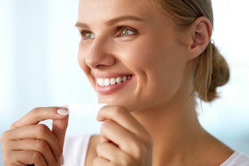 Woman With Healthy White Teeth Using Teeth Whitening Strip. High Resolution Image