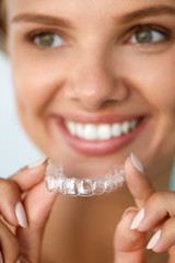 Smiling Woman With White Teeth Holding Teeth Whitening Tray. High Resolution Image