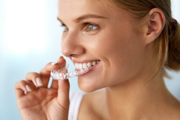 Smiling Woman With Beautiful Smile Using Invisible Teeth Trainer. High Resolution Image