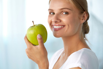Woman With Apple. Beautiful Girl With White Smile, Healthy Teeth. High Resolution Image