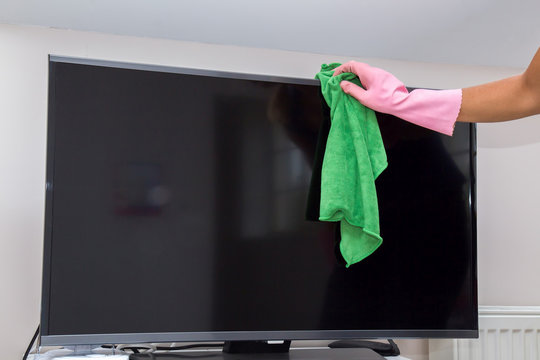 Hand in protective glove carefully cleaning TV screen from dust. Screen shining. Regular clean up. Maid cleans house.
