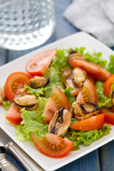 salad with tomato and mussels on white dish