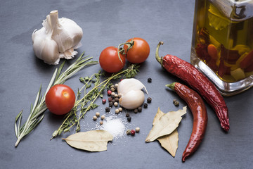 Dry red hot chili peppers, garlic, laurel leafs, tomatoes, seasoning, rosemary and savory on a dark background
