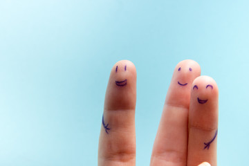 Three smiling fingers that are very happy to be friends. Friendship teamwork concept on blue background with copy space for ad text.