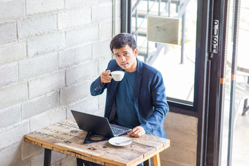 businessman wear suit using laptop and drinking latte coffee