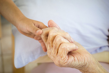 Hand of an old person or senior holding child's hand. Grandmother holding grandson's hand.