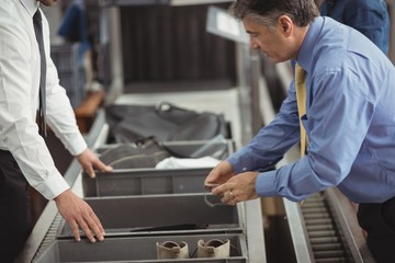 Man putting watch into tray for security check