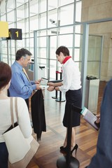 Businessman showing his boarding pass at the check-in counter