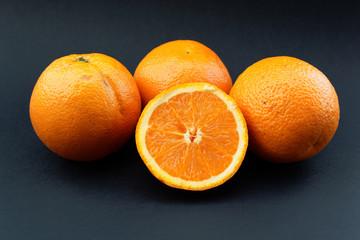 Fresh oranges on black background