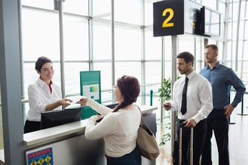Woman giving her passport to airline check-in attendant