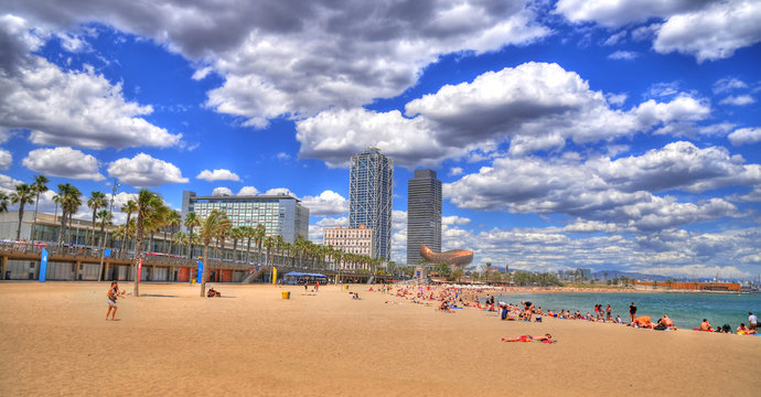Panoramip colorful HDR image of tourists at Barcelona Beach near Port Olimpic in summer 2016 in Barcelona, Spain. It is one of the most popular beach in Europe