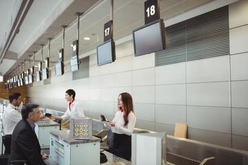 Airline check-in attendant handing passport to passenger