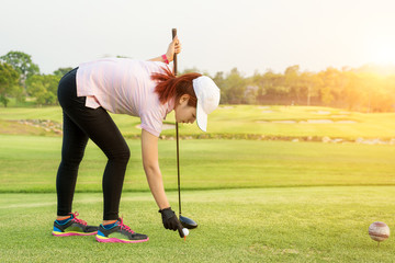 Asian woman putting golf ball on tee to already to play golf.