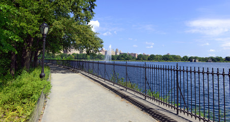 Central Park reservoir with fountain with Upper West Side skyline and blue sky with clouds, Manhattan, New York City