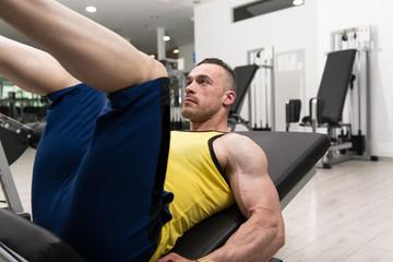 Man In Gym On Machine Exercising