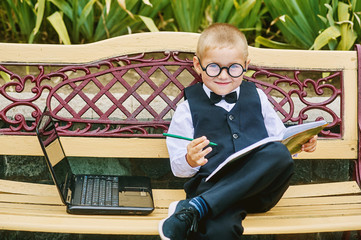 beautiful boy in glasses sits with the laptop . preschool education