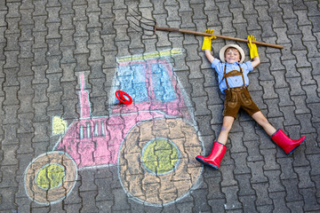 little kid boy having fun with tractor chalks picture