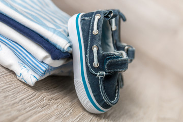 Folded blue and white bodysuit with shoes on it on grey wooden background. diaper for newborn boy. Stack of infant clothing. Child outfit. Copy space.