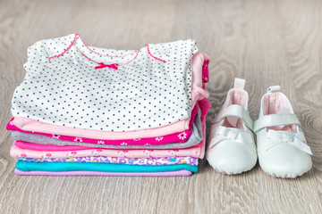 Folded pink and white bodysuit with shoes on it on grey wooden background. diaper for newborn girl. Stack of infant clothing. Child outfit. Close up.