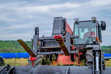 Wall Mural - Loader in the field on a background cloudy sky.