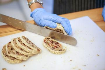 Baker Slicing Bran Bread on a Cutting Board