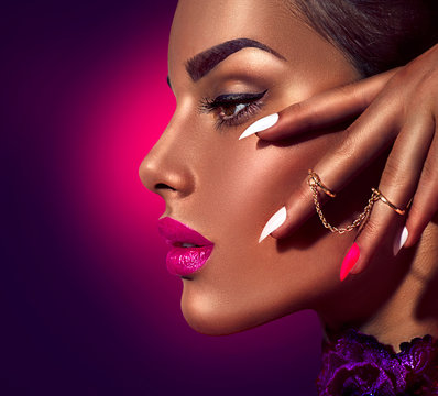 Sexy model with brown skin and purple lips over dark background