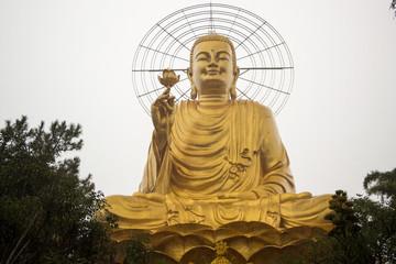 Golden Buddha statue under rain in the city of Dalat in Vietnam