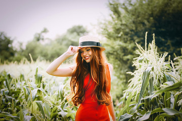red-haired girl with freckles in red dress walking on a field of corn she is smiling a