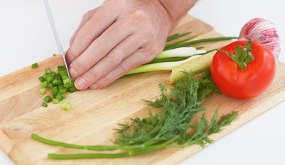 Closeup man's hand with a knife cutting green onion on a wodden board.