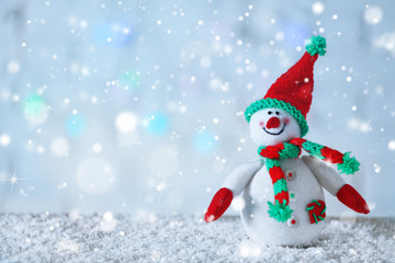 Cute snowman on Christmas background. Snow effect