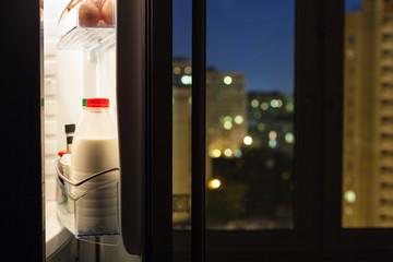 door of home fridge with milk bottles in night