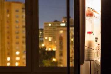 Open door of home fridge and urban view in night