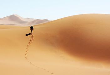 Mann laeuft durch die Wüste von Namibia