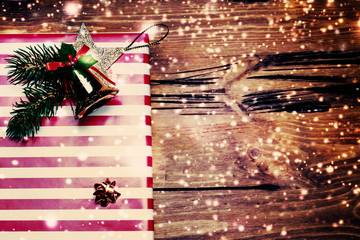 Christmas Present wrapped in red paper on a wooden background wi