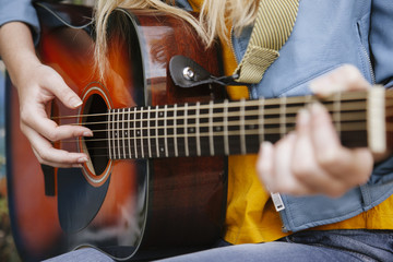 fingers playing acoustic guitar