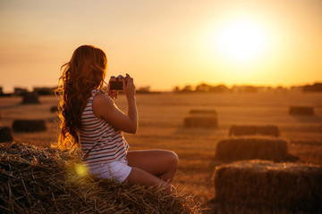 beautiful young redhead woman with vintage camera