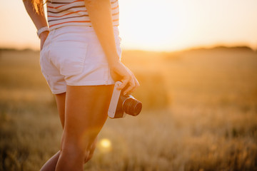 beautiful young woman holding a vintage camera at hip level
