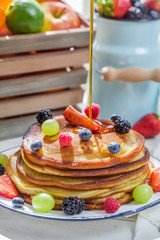 Pancakes with fruits poured maple syrup