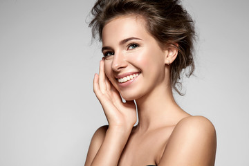 Beautiful smiling girl with clean skin, natural make-up, and white teeth on grey background Wall mural