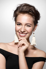 Beautiful girl with a charming smile in a black dress and earrings tassels