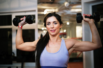 Fit woman show her power with weight in gym