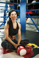 Fit attractive woman sits on boxing ring in gym